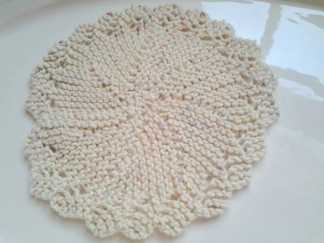 Knitted circular dishcloth, made from the tail end of a cone of cotton yarn.  I like it!